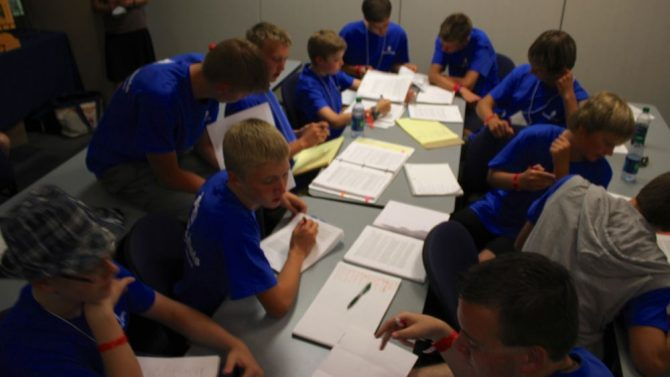 "Here's a camp picture of students working together to come up with the best arguments against a case given by their coach. This is ""training for action."""