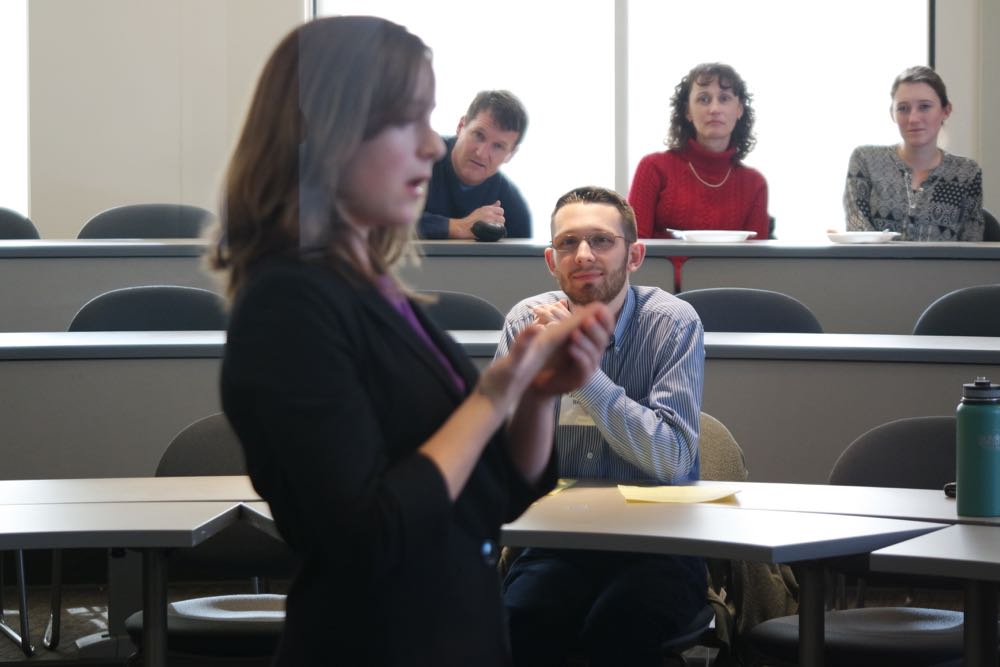 Judges and others observe a student performance at a speech competition.